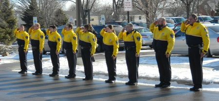 Campus Safety officers saluting a funeral procession.